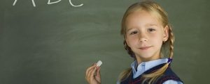 Little, pretty girl standing in front of blackboard. Holding chalk. Smiling and looking at camera